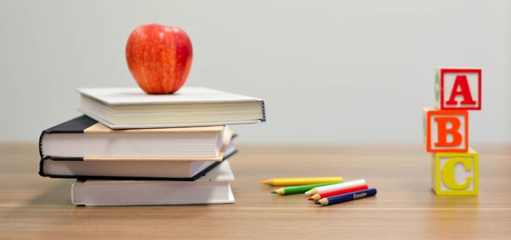 Books, Apple, Pencils, and Blocks on Desk