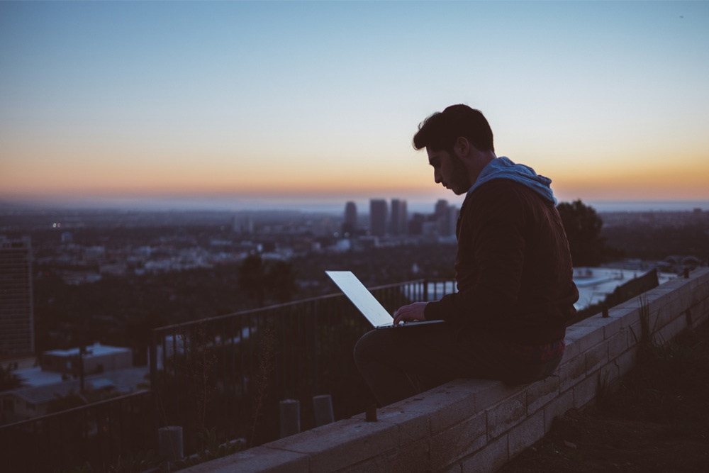 Man with Laptop on Hill Overlooking City