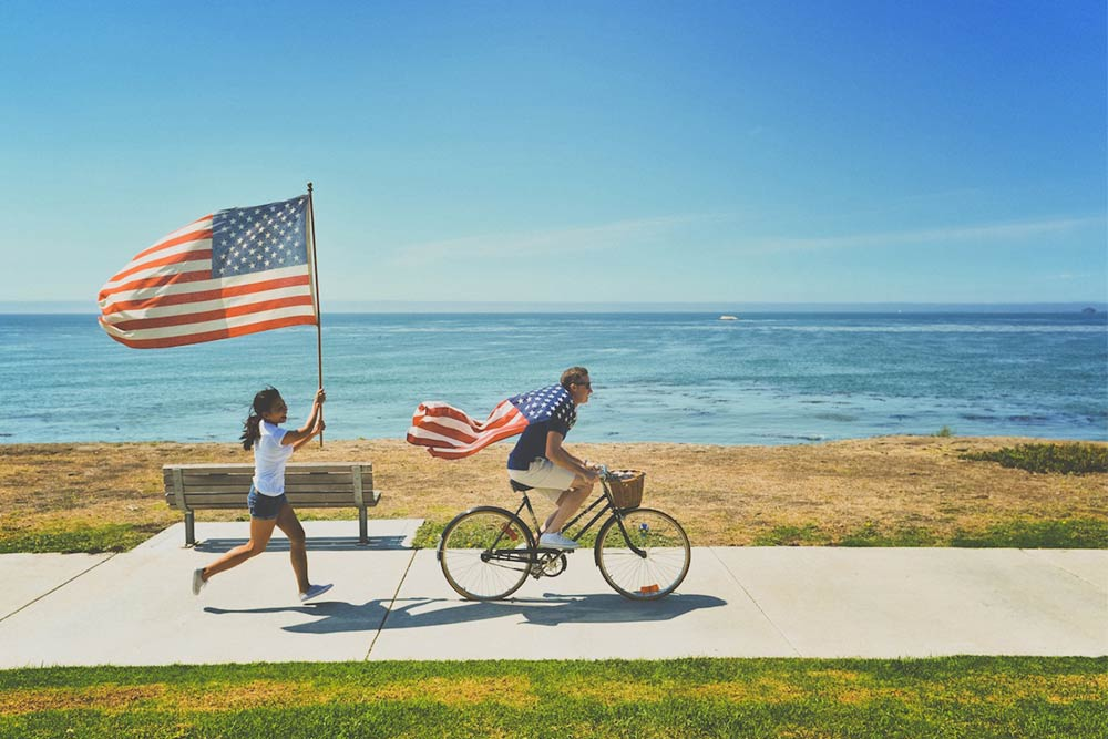 People Running and Biking with American Flag