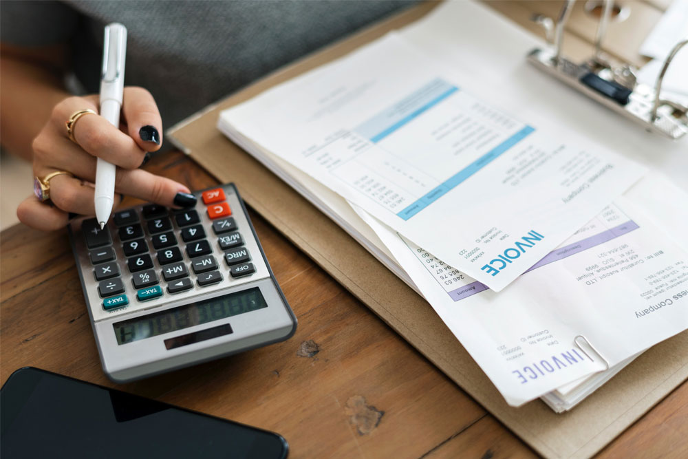 Woman with Calculator and Invoice