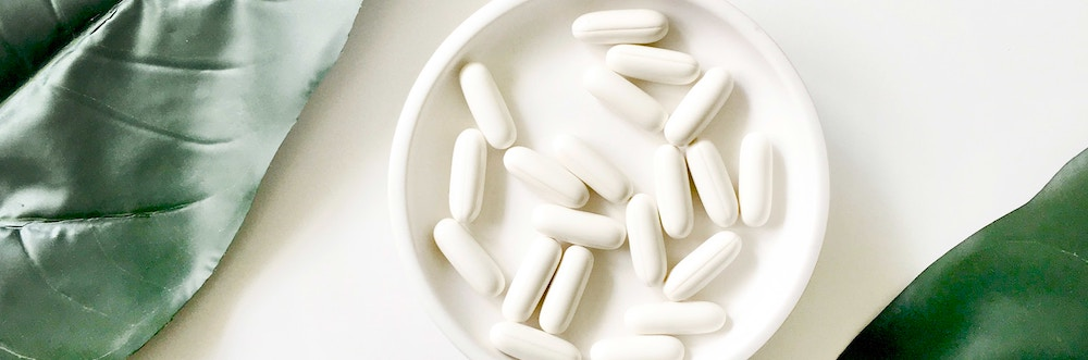White pills in a white dish surrounded by big, green leaves.